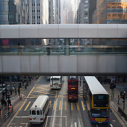 The view from a walkway in Central, the finance district of Hong Kong, of tall buildings made of glass and steel.