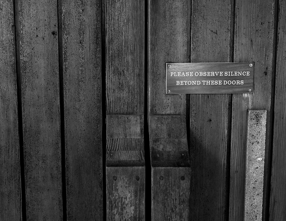 """A sign on the chapel door at the Hermitage. The chapel, along with a bookstore, gardens and cabins for overnight stays, are areas of the property members of the public can openly visit.<br /> <br /> """"Silence and solitude are practices. If they don't end up in love, they're worthless,"""" say Father Cyprian, the current Prior. """"If you don't come out of silence more loving and kind, you're doing something wrong.""""<br /> <br /> Cyprian, 60, joined the New Camaldoli Hermitage in 1992 at age 34. He was a professional musician before becoming a monk."""