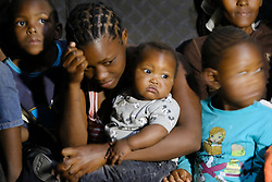 JOHANNESBURG, SOUTH AFRICA - APRIL 14: Children in a room during a visit by Johannesburg Mayor, Geoffrey Makhubo. The mayor visited Alexandra to address community concerns from the effects of the national lockdown on April 14, 2020 in Johannesburg South Africa. Under pressure from a global pandemic. President Ramaphosa declared a 21 day national lockdown extended by another two weeks, mobilising goverment structures accross the nation to combat the rapidly spreading COVID-19 virus - the lockdown requires businesses to close and the public to stay at home during this period, unless part of approved essential services. (Photo by Dino Lloyd)