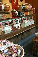 """Sembei Shop, Yanaka - The Japanese love crackers of many different descriptions, spicy ones, crackers with seaweed imbedded in them, sesame crackers. This is a traditional cracker or """"sembai"""" shop in Yanaka, Tokyo. Note the large round bowls to protect crackers from the elements."""