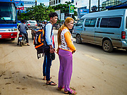 05 JULY 2017 - POIPET, CAMBODIA: Cambodian migrant workers who just returned to Cambodia from neighboring Thailand cross the main road in Poipet, Cambodia. The Thai government proposed new rules for foreign workers recently. The new rules include fines of between 400,000 and 800,00 Thai Baht ($12,000 - $24,000 US) and jail sentences of up to five years for illegal workers and people who hire illegal workers. Hundreds of companies fired their Cambodian and Burmese workers and tens of thousands of workers left Thailand to return to their countries of origin. Employers and human rights activists complained about the severity of the punishment and sudden implementation of the rules. On Tuesday, 4 July, the Thai government suspended the new rules for 180 days and the Cambodian and Myanmar governments urged their citizens to stay in Thailand, but the exodus of workers continued through Wednesday.     PHOTO BY JACK KURTZ