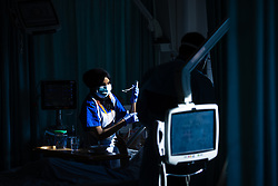 © Licensed to London News Pictures . 12/02/2021 .  Manchester , UK . Registered Nurse TASNIM AHMED (23) provides care for a patient on a bay on Ward 4 , the Respiratory Cohort Area . Inside Manchester Royal Infirmary , where patients are being treated for the effects of Coronavirus . Photo credit : Joel Goodman/LNP