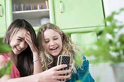 Girls in kitchen with smart phone