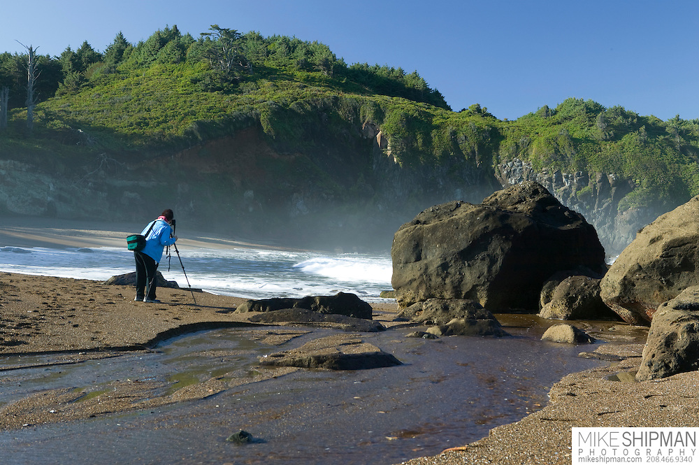 A woman wearing a blue jacket photographs the surf on Fogarty Beach, Oregon