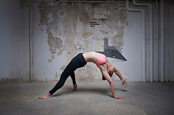 Mid adult woman practicing wild thing pose in yoga studio, Munich, Bavaria, Germany
