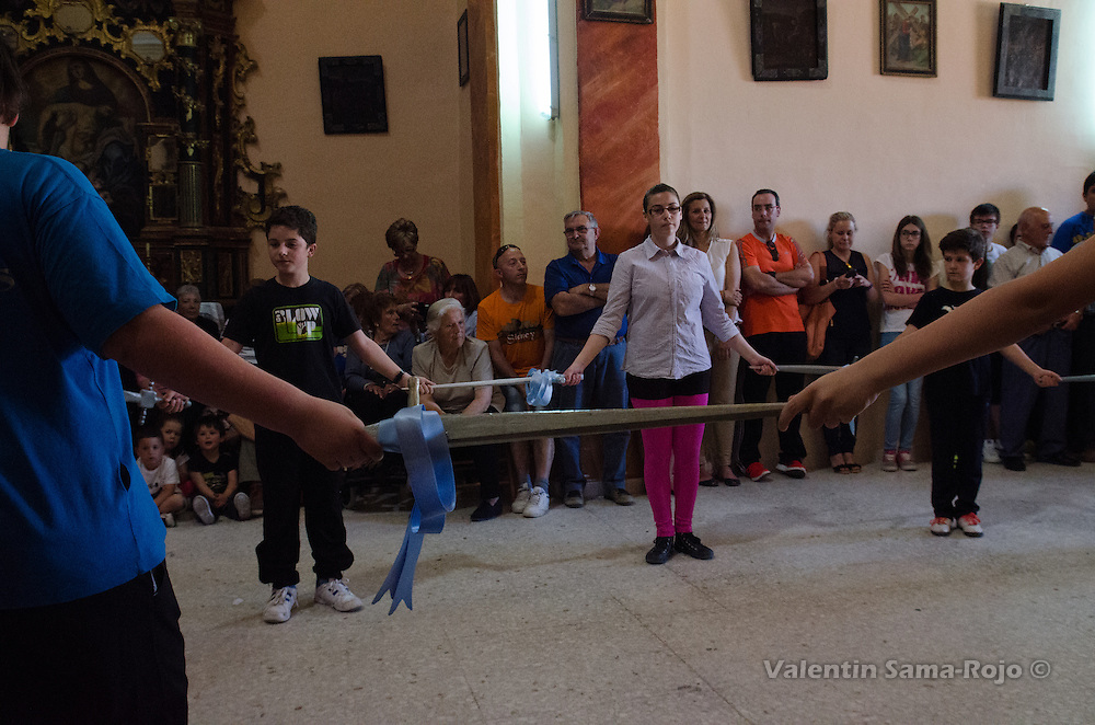 Kids holding a wood sword decorated with a blue ribbon during the rehearsal of Cetina's Dance in 'San Juan Lorenzo' hermitage.
