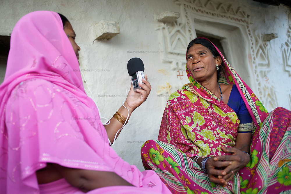 Dharkan 107.8 program-maker Ramvati Adivasi records an interview with an Adivasi (tribal, or Scheduled Tribe) woman in the village of Patara, 20km from Shivpuri. Adivasi is is an ASHA (local female health advisor). She provides a free referral service to local women, keeping them in touch with government health services. Adivasi receives a fee from the government for every referral. This is one means by which the government and partners UNICEF are increasing the rate of institutional deliveries in Madhya Pradesh state. Adivasi has recorded several programs informing women of government health services. ..Shivpuri district in Madhya Pradesh suffers from poor health outcomes. Of particular concern is the high rate of maternal mortality. One of the Indian government's aims, with partners Unicef, is to encourage the population to adopt practices to improve sanitation and health practices. In an area made up of traditionally disadvantage groups and suffering low literacy rates, this can be a challenge. ..A survey found that radio was the most readily accessible media by the Shivpuri community with more than half saying they tuned in several times a day. ..Dharkan 107.8 FM will go on air in July. The station that will broadcast to 75 villages in a 15-kilometer radius reaching 170,000 people...Rather than preaching educational messages, the station, which is already producing pilot programs, uses humor and folk artists performing in the local language to entertain and inform their audiences. There is a major impact, especially on women, who are contributing their voices to such wide-ranging issues as caste discrimination, female feticide and women,A?o?s empowerment. ..Photo: Tom Pietrasik.Shivpuri, Madhya Pradeh. India.June 2009