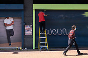Man on a ladder painting the exterior of a shop interacts with a printed picture of a model whose head is obscured by shutters on 14th July 2021 in Birmingham, United Kingdom. The figures are in scale with one another despite being real in 3D or two dimensional.