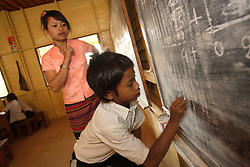 An unnamed child works on the blackboard in a new classroom in the afternoon session.  AusAid funded the construction of this and other classrooms building Ban Chaling, Dakcheung, near Sekong, Lao PDR