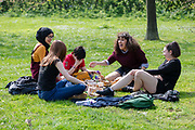 A group of young women chat and laugh as they enjoy a picnic lunch on the grass in Regents Park in London, England on April 17, 2019.