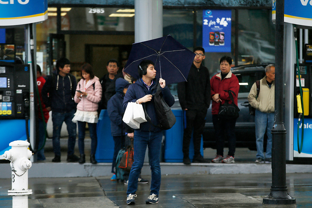 People take cover from the rain under a gas station roof as they wait at a bus stop on Sunday, Feb. 3, 2019, in San Francisco, Calif.