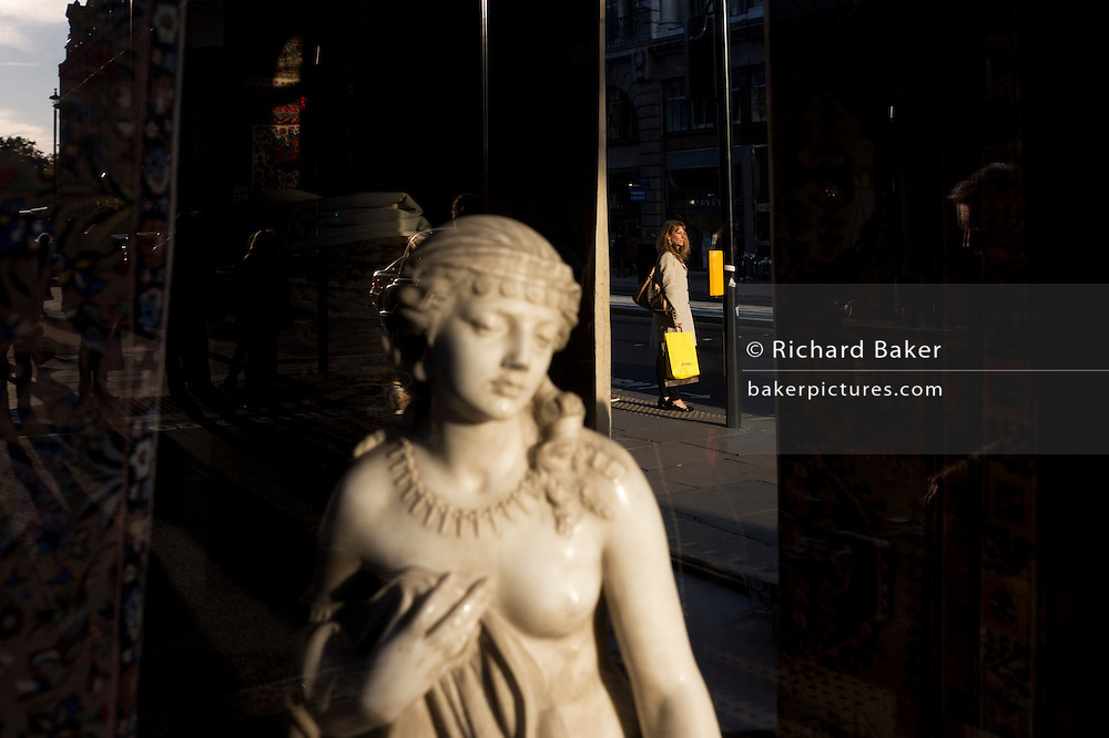 Woman waits to cross road with small girl statue credited to the 19th century Florence-born artist Raffaello Romanelli.