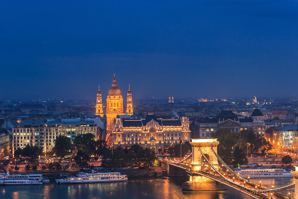 The Chain Bridge, Gresham Palace, and St. Stephen's Basilica in Budapest, Hungary. These three landmarks create a fascinating evening vista over the Danube. Gresham Palace, which is nowadays a luxury Four Seasons hotel is an excellent example of Art Nouveau architecture.