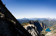 A hiker looks out from the summit of Vesper Peak, North Cascades, Washington.
