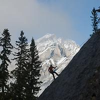Sasha Ruttan rappels down a face at Rundle Rock, below Cascade Mountain, near Banff, Alberta, in Canada's Banff National Park.
