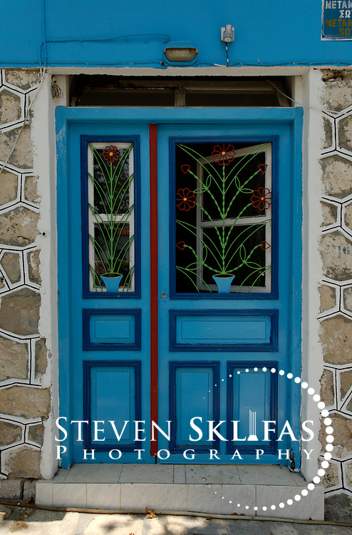Samos. Greece.  View of blue door of a stone house in the town of Pythagoreio which is the most popular and fashionable town on the island and was named after the great philosopher Pythaogaras who was born here in 580 BC.