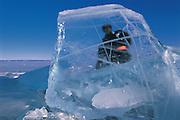 Darkhad man<br /> Ice chunks on lake shore<br /> Lake Hovskol<br /> Mongolia