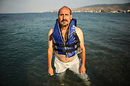 A Christian Syrian refugee poses for a portrait with a lifejacket that he used to cross the Aegean Sea along Lambi Beach in Kos, Greece on July 1, 2015.