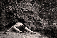 nude of woman under ivy plant