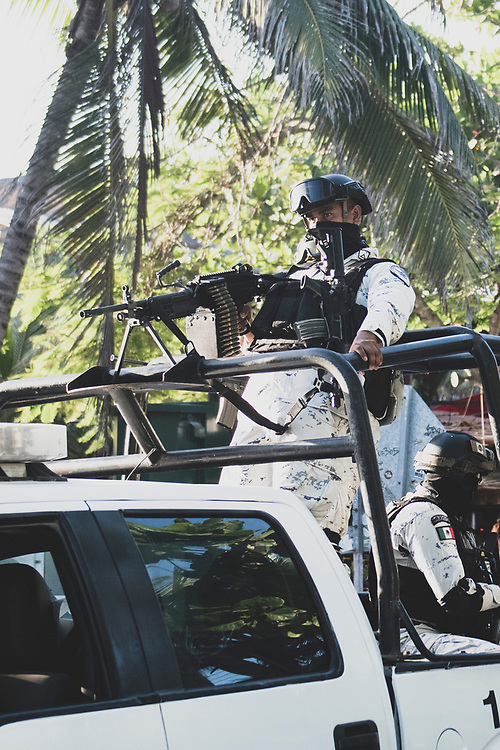Tulum, Mexico - May 12, 2021: Mexican National Guard security forces ride toward the scene of a shooting in the busy tourist area of Tulum's hotel zone. Tourists are seen walking in the background.