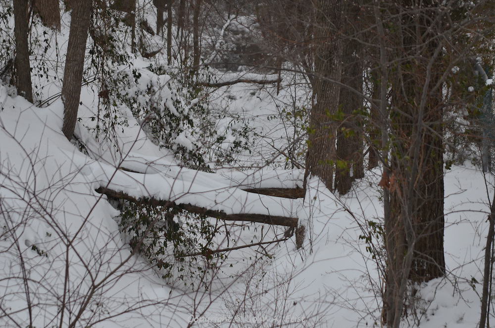 A couple of snow covered logs over a snow covered stream following a big storm