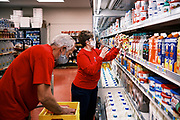 "03 AUGUST 2020 - JEWELL, IOWA:  Employees stock the dairy section of the Jewell Market. The only grocery store in Jewell, a small community in central Iowa, closed in 2019. It served four communities within a 20 mile radius of Jewell. Some of the town's residents created a cooperative to reopen the store. They sold shares to the co-op and  held fundraisers through the spring. Organizers raised about $225,000 and bought the store, which had its ""soft opening"" July 8. The store celebrated its official reopening Monday August 3. Before the reopening, Jewell had been a ""food desert"" for seven months. The USDA defines rural food deserts as having at least 500 people in a census tract living 10 miles from a large grocery store or supermarket. There is a convenience store in Jewell, but it sells mostly heavily processed, unhealthy snack foods that are high in fat, sugar, and salt.         PHOTO BY JACK KURTZ"
