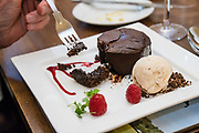 Dining on a dessert of chocolate cake and ice cream with raspberries at Irton Hall, a large, mostly 1800s house with a 1300s tower; now offering luxurious Bed & Breakfast accommodation in Lake District National Park, Cumbria county, England, United Kingdom, Europe.  England Coast to Coast hike with Wilderness Travel, day 1 of 14. [This image, commissioned by Wilderness Travel, is not available to any other agency providing group travel in the UK, but may otherwise be licensable from Tom Dempsey – please inquire at PhotoSeek.com.]