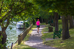 A woman enjoys a jog along the towpath beside the River Thames at Old Windsor, Berkshire. Old Windsor, Berkshire, July 05 2019.