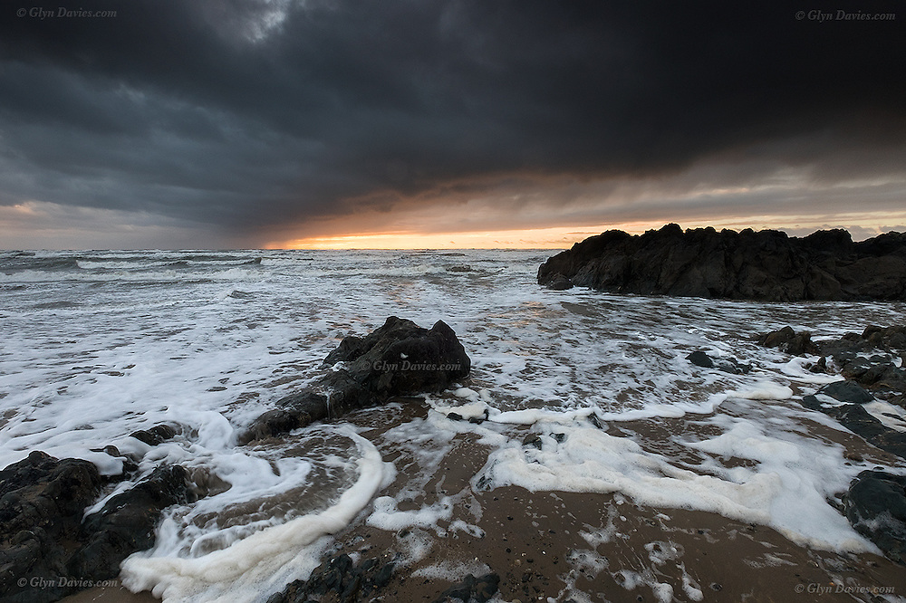 Successive storm waves during bad, gale driven weather, create piles of wind blown foam on the incoming tide at sunset in Winter at this West Anglesey beach near Rhosneigr