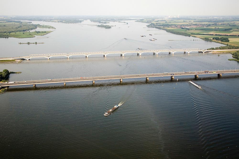 Nederland, Zuid-Holland, Hollandsch Diep, 04-07-2006;  binnenvaartschepen op het Hollandsch Diep met de Moerdijkbruggen: in de midden de brug voor het autoverkeer (A16), daarachter de nieuwe brug voor de HSontworpen door Benthem Crouwel; verscholen achter de HSL-brug de oude spoorbrug; in de achtergrond:  links de Dordtsche Biesbosch, met de monding van de Nieuwe Merwede; rechts de rivier de Amer (overgaand in Bergsche Maas) met Biesbosch (NationaaPark Biesbos)..Zie ook andere foto's van deze lokatie (lucht en panorama); deevan de serie Panorama Nederland. .Barges pass the Moerdijk bridges, in the rear the new railway bridge for the TGV (HST), the bridge is located next to the existing raibridge..Other aerial and panorama photos available, part of the series Panorama Nederland (major infrastucture photo project).luchtfoto (toeslag); aerial photo (additional fee required); .foto Siebe Swart / photo Siebe Swart