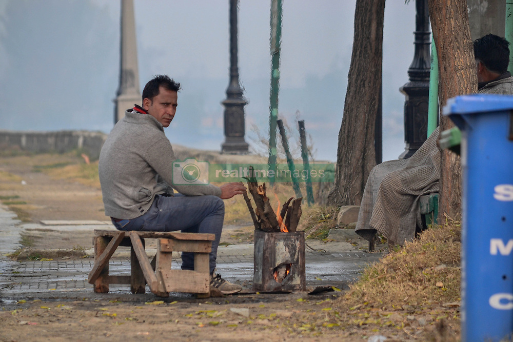 November 11, 2018 - Srinagar, J&K, India - A local man seen seated next to a fire stove to warm himself at the roadside during a cold and foggy morning in Srinagar.The night temperature witnessed improvement as the mercury surged and settled several degree above normal in majority of the places in Kashmir valley, where rain and snow is predicted for four days from Sunday under the influence of a Western Disturbance (WD), which is active in the region. However, the day chill intensified across Kashmir valley due to overcast conditions coupled with ice cold winds. (Credit Image: © Saqib Majeed/SOPA Images via ZUMA Wire)