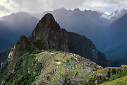 """A rain storm breaks over Machu Picchu, a magnificent Inca archeological site in the Cordillera Vilcabamba, Andes mountains, Peru, South America. Machu Picchu was built around 1450 AD as an estate for the Inca emperor Pachacuti (14381472). Spaniards passed in the river valley below but never discovered Machu Picchu during their conquest of the Incas 1532-1572. The outside world was unaware of the """"Lost City of the Incas"""" until revealed by American historian Hiram Bingham in 1911. Machu Picchu perches at 2430 meters elevation (7970 feet) on a well defended ridge 450 meters (1480 ft) above a loop of the Urubamba/Vilcanota River ( Sacred Valley of the Incas). UNESCO honored the Historic Sanctuary of Machu Picchu on the World Heritage List in 1983."""