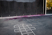 """Paint near children's hopscotch at town hall, or ajuntament, of Sant Cugat del Valles, Barcelona. The paint was thrown at a poster, which replaces an earlier one torn down by far-right protestors, reads """"Liibertat Presos Politics"""" - Freedom for Political Prisoners in support of Catalan government ministers and civil society leaders jailed by Spanish government.  This version has been bombarded with paint bombs."""
