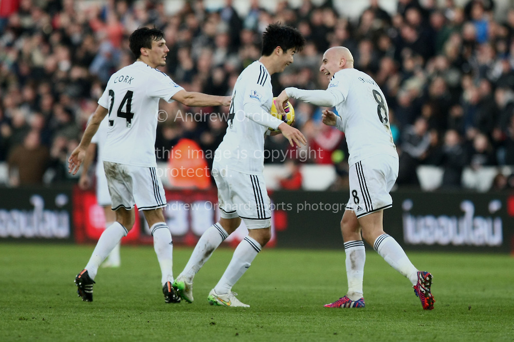 Ki Sung-Yueng of Swansea (centre) celebrates scoring his side's first goal with Jonjo Shelvey (right) and Jack Cork. <br /> Barclays Premier League match, Swansea City v Sunderland at the Liberty stadium in Swansea, South Wales on Saturday 7th Feb 2015.<br /> pic by Mark Hawkins, Andrew Orchard sports photography.