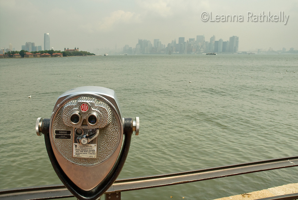 Metered binoculars look to the Manhattan skyline,  New York City, from Liberty Island.