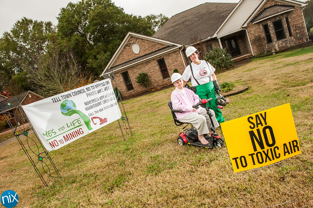 Harrisburg resident Bryce Goebel, wearing a hazmat suit, pictured with her mother Linda Ritch, at their home along Pharr Mill Road, is helping to lead the opposition to a proposed granite mining operation with an asphalt plant nearby. Goebel and her neighbors have placed signs in their yards and plan to make their voices heard during a public hearing in Harrisburg on Monday.