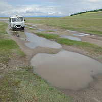 MONGOLIA.   Four-wheel drive van splashes through puddles in southern Darhad Valley.  This road washes out regularly in summertime rainstorms that turn it into impassable, boggy mud.