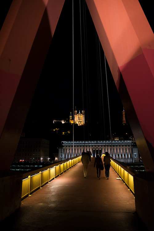Pedestrians cross the Passerelle du Palais de Justice (or Gateway Courthouse), a suspended footbridge with a single pylon across the Saone River in Lyon, France. The church on the hill is Notre-Dame de Fourvière.