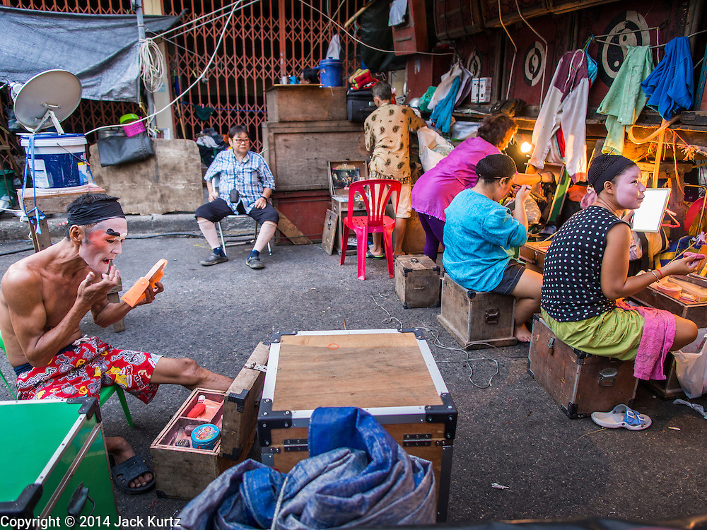 """18 AUGUST 2014 - BANGKOK, THAILAND: Members of the Lehigh Leng Kaitoung Opera troupe put on their makeup before a performance at Chaomae Thapthim Shrine, a small Chinese shrine in a working class neighborhood of Bangkok. The performance was for Ghost Month. Chinese opera was once very popular in Thailand, where it is called """"Ngiew."""" It is usually performed in the Teochew language. Millions of Chinese emigrated to Thailand (then Siam) in the 18th and 19th centuries and brought their culture with them. Recently the popularity of ngiew has faded as people turn to performances of opera on DVD or movies. There are still as many 30 Chinese opera troupes left in Bangkok and its environs. They are especially busy during Chinese New Year and Chinese holiday when they travel from Chinese temple to Chinese temple performing on stages they put up in streets near the temple, sometimes sleeping on hammocks they sling under their stage. Most of the Chinese operas from Bangkok travel to Malaysia for Ghost Month, leaving just a few to perform in Bangkok.      PHOTO BY JACK KURTZ"""