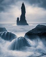 Dramatic black and white image of seastacks and crashing waves along the south coast of Iceland
