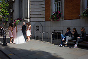 People watch a bride and bridesmaids from a civil wedding ceremony outside Chelsea Registry Office. The mid-afternoon ceremony is due to take place soon and the wedding bridal group have stopped in the street to pose for pictures, the light from behind shines on the bride's white dress and the heels of her bridesmaids. Three others look on from a bench in the shade, amused and entertained by the formality and prosperity of those taking part.
