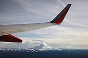 """SHOT 1/26/11 4:59:18 PM - Mount Rainier as seen out the window of a Southwest Airlines flight. Mount Rainier is a massive stratovolcano located 54 miles (87 km) southeast of Seattle, United States. It is the most prominent mountain in the contiguous United States and the Cascade Volcanic Arc, with a summit elevation of 14,411 feet (4,392 m). Mt. Rainier is considered one of the most dangerous volcanoes in the world, and it is on the Decade Volcano list. Seattle is the northernmost major city in the contiguous United States, and the largest city in the Pacific Northwest and in the state of Washington. A seaport situated on a narrow isthmus between Puget Sound (an arm of the Pacific Ocean) and Lake Washington, about 100 miles (160 km) south of the Canada - United States border, it is named after Chief Sealth """"Seattle"""", of the Duwamish and Suquamish native tribes. Seattle is the center of the Seattle-Tacoma-Bellevue metropolitan statistical area, the 15th largest in the United States, and the largest in the northwestern United States. Seattle is the county seat of King County and is the major economic, cultural and educational center in the region. (Photo by Marc Piscotty / © 2011)"""