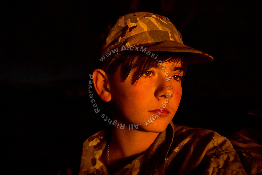A youngster participating to the ultra-nationalistic Azovets children's camp is listening attentively to his instructors, during the evening around the campfire, on the banks of the Dnieper river in Kiev, Ukraine's capital.