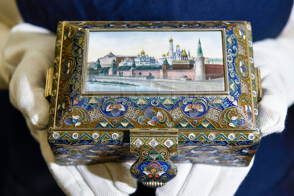 """© Licensed to London News Pictures. 22/11/2019. LONDON, UK. A technician presents """"A silver-gilt, cloisonné and pictorial enamel casket"""", 1908-1917, by Feodor Ruckert, Moscow (Est. GBP100-150k) at the preview for the upcoming sales of Russian artworks at Sotheby's New Bond Street.  The Russian Pictures and Works of Art, Fabergé and Icons sales take place on 26 November.  Photo credit: Stephen Chung/LNP"""