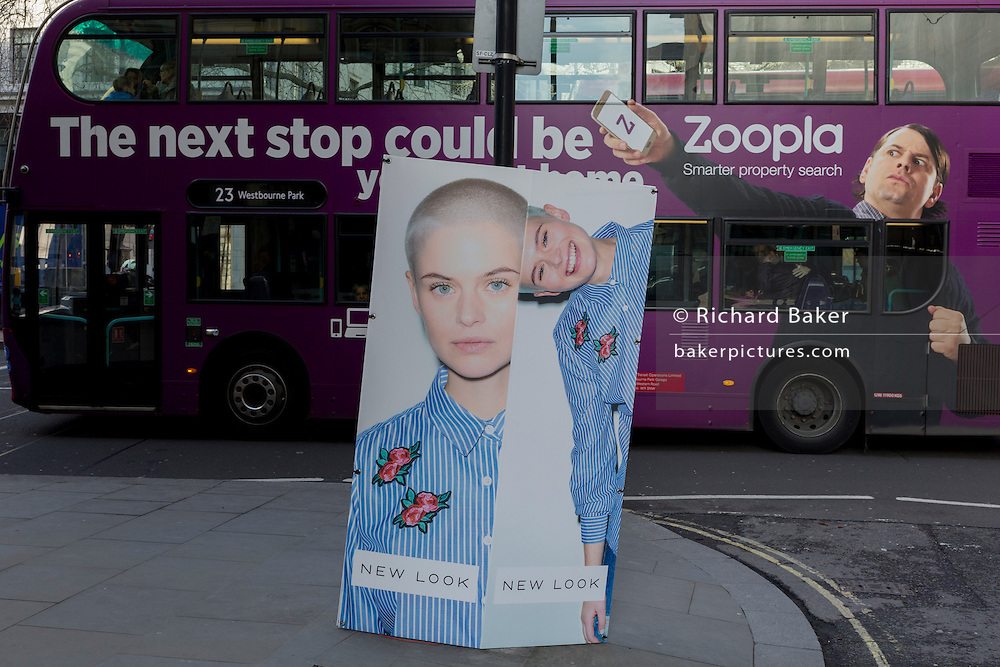 "A bus ad for property website Zoopla passes the London Fashion Week in the Strand, on 17th Febriary 2017, in London, England, United Kingdom. London Fashion Week is a clothing trade show held in London twice each year, in February and September. It is one of the ""Big Four"" fashion weeks, along with the New York, Milan and Paris. The fashion sector plays a significant role in the UK economy with London Fashion Week alone estimated to rake in £269 million each season. The six-day industry event allows designers to show their collections to buyers, journalists and celebrities and also maintains the city's status as a top fashion capital. (Photo by Richard Baker / In Pictures via Getty Images)"