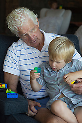 little boy sitting on his grandfather's lap while they play together with legos at home