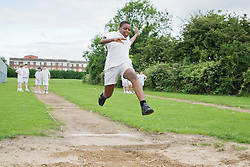 Secondary school students taking part in long jump competition,