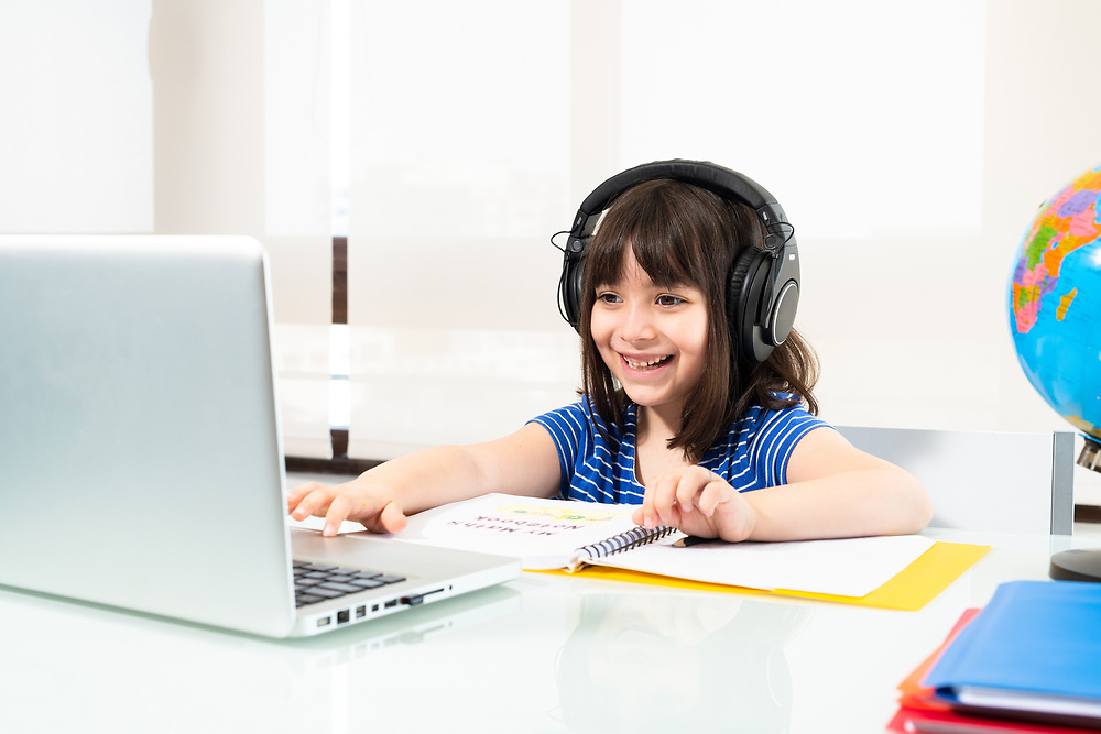 A little girl of 6 years old from first grade old homeschooling through video conference.