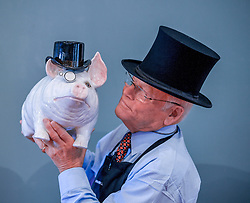 Pictured: Sidney Drew from Lyon & Turnbull with the Wemyss ware pottery pig.<br /> <br /> Lyon & Turnbull's Scottish silver and applied arts sale includes some rare items, including a large Wemyss ware porcelain pig, complete with top hat and monocle from 1900, estimated to fetch £4000 to £6000 GBP.<br /> <br /> © Dave Johnston / EEm