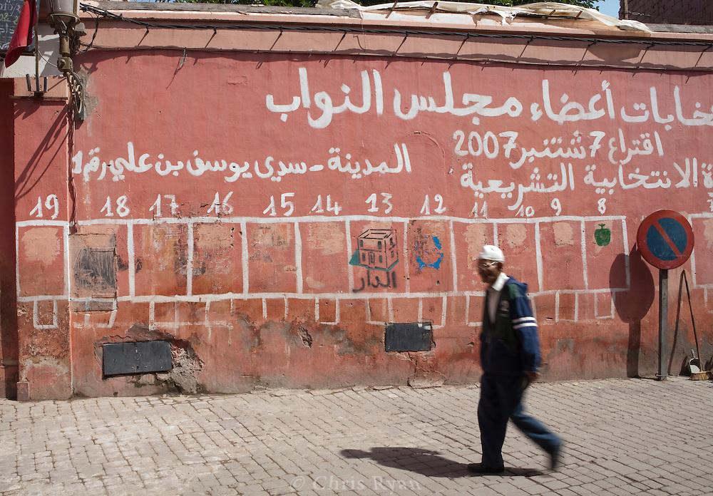 Man walking past wall mural of political party symbols, Marrakesh, Morocco